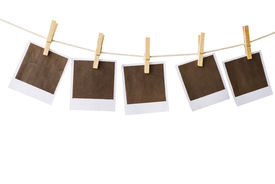 foto of polaroid  - Old polaroid film blanks hanging on a rope held by clothespins - JPG