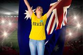 Excited football fan in brasil tshirt holding australia flag against vast football stadium with fans