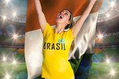 Pretty football fan in brasil t-shirt holding ivory coast flag against large football stadium with brasilian fans
