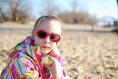 girl wearing sunglasses eating sandwich at the sandy beach