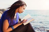 stock photo of single woman  - Beautiful Girl reading her Bible by the sea - JPG