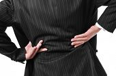 stock photo of spinal disc  - man wearing a suit with his hands in his low back because of his low back pain - JPG