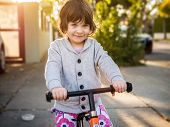 Three year old girl learning to ride bicycle outdoors