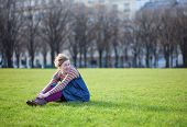Beautiful Young Girl In Bright Clothes Sitting On The Grass