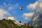 Majestic medieval Palase Hohenwerfen. Over the castle and the mountains in the clouds flying the giant balloon