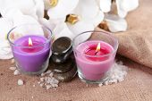 Composition with beautiful colorful candles, sea salt and orchid flowers, on wooden background