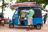 WELIGAMA, SRI LANKA - MARCH 7, 2014: Driver stand in front of blue tuk tuk vehicle transporting surf