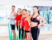 fitness, sport, training, gym and lifestyle concept - group of smiling people working out with rubbe