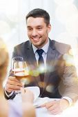 restaurant, couple and holiday concept - smiling young man with glass of red wine looking at girlfri