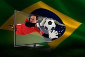 Composite image of fit goal keeper saving goal through tv against brazilian flag waving