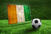 Black and white football on grass against ivory coast flag in grunge effect