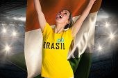 Pretty football fan in brasil t-shirt holding ivory coast flag against large football stadium with fans in blue