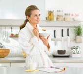 Young Woman Eating Muesli In Kitchen In The Morning