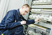 stock photo of electrician  - electrician engineer worker inspector  in front of fuseboard equipment in room - JPG