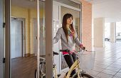 Girl with fixie bike opening a glass door to exit