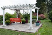 image of gazebo  - A large white wooden gazebo structure on a concrete platform and a red bench underneath in a landscaped yard - JPG