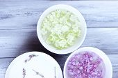 stock photo of perfume  - Aromatherapy treatment bowls with flowers and perfumed water on wooden background - JPG