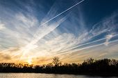 stock photo of unnatural  - beautiful sunset over the lake with what looks like manufactured cloud formations from airplanes all over the area with metallic shiny colors - JPG