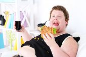 Fat man eating tasty sandwich and drink coke on home interior background