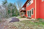 picture of red siding  - Red clapboard siding house. View of walkout deck and forest