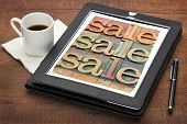 sale word abstract in stained letterpress wood type on a digital tablet with a cup of coffee
