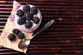 Healthy breakfast - yogurt with  blackberries and muesli served in glass jar, on dark  background