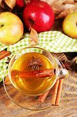 Composition of  apple cider with cinnamon sticks, fresh apples and autumn leaves on wooden background