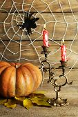 Halloween decoration with spider on web, pumpkin and candles on wooden background