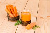 Carrot juice and slices on wood.