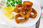 Calamari fried with lemon and fork on plate