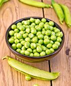 Green peas in brown bowl on board