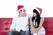 Couple Wearing Christmas Hats On Couch