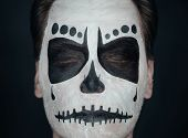 picture of sugar skulls  - Portrait of young man with closed eyes and sugar skull makeup - JPG