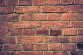 Weathered red brick wall background with vignette eccet, grungy rusty blocks ofcolorful horizontal architecture