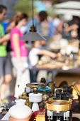 stock photo of flea  - Market boot with objects beeing selled at the weekend flea market in the city center. Curious visitors in the background.