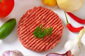 raw beef burger with colorful peppers, onion and garlic