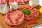 two raw minced beef burgers with onion, garlic and pink pepper, served on the wooden cutting board