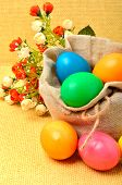 Easter Colored Eggs In The Sack With Flowers