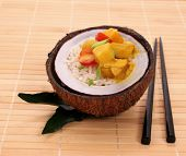 Oconut With Rice And Curry Chicken On Bamboo Background
