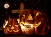 Creepy decorations for Halloween night, glowing carved pumpkins with scary horrible spiders, cross and burning flame on the graveyard in full moon night