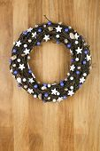 Decorated Christmas Door Wreath White Stars And Blue Pearls On Sapele Wood Background