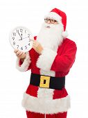 christmas, holidays and people concept - man in costume of santa claus with clock showing twelve pointing finger