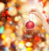 christmas, decoration, holidays and people concept - close up of woman hand holding christmas ball over red lights background