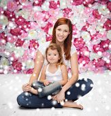 childhood, parenting and people concept - happy mother with little girl over wooden floor and flowers background