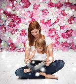 childhood, parenting, people and technology concept - happy mother with little girl and tablet pc computer over wooden floor and flowers background