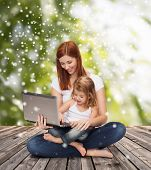 childhood, parenting, people and technology concept - happy mother with little girl with laptop computer over wooden floor and green plants background