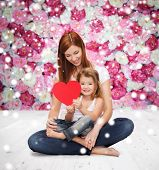 childhood, parenting, love and people concept - happy mother with little girl and red heart over wooden floor and flowers background