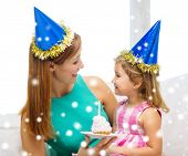 family, childhood, holidays and people concept - happy mother and daughter in blue party hats with cake and candle