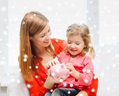 family, childhood, holidays, finances and people concept - happy mother and daughter with piggy bank