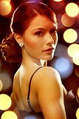 luxury, vip, nightlife, party concept - beautiful woman in evening dress wearing diamond earrings